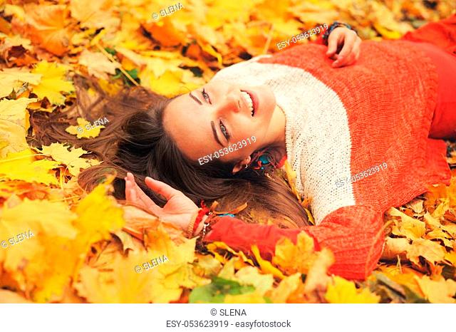 Happy woman autumn portrait, lying in autumn leaves, dressed in fashion sweater