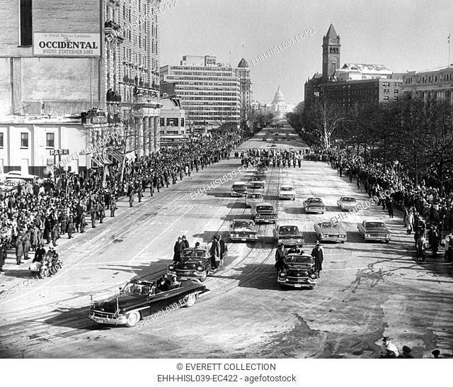 President John Kennedy and First Lady Jacqueline Kennedy in lead car of the Inaugural Parade. The parade stretches up Pennsylvania Avenue to the distant Capitol