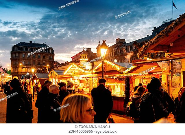 STRASBOURG, FRANCE - 9 DEC 2016: Crowd visiting the oldest Christmas Market worldwide in central Strasbourg, Alsace with multiple Christmas market stalls