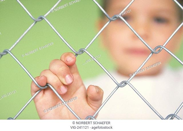 portrait, close-up, hand of a boy, 6 years, holding the wire of a netting fence  - GERMANY, 23/11/2003