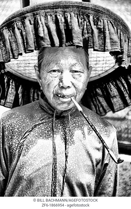 Old Hakka woman with pipe in the old walled city of Kam Tin in the New Territories area of Hong Kong  This is a dying breed of woman for tourists with black...