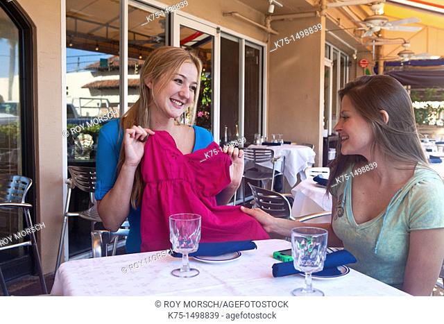 Two friends at outdoor cafe showing off new purchase