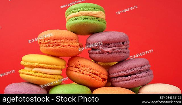 yellow, purple, green round baked macarons cakes on a red background, close up