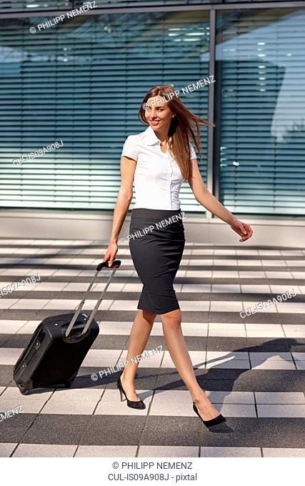 Young businesswoman walking with trolley luggage over pedestrian crossing