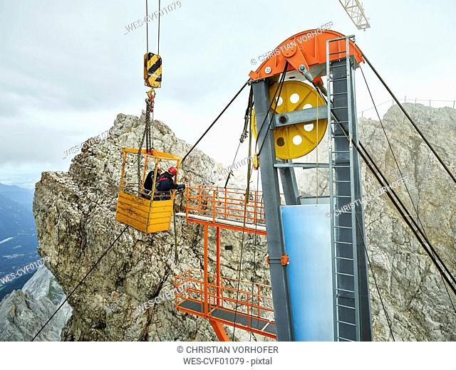 Germany, Bavaria, Garmisch-Partenkirchen, Zugspitze, installers working on goods cable lift in a work cage