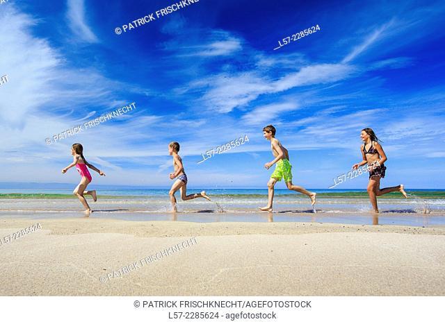children running along sandy beach, Scotland