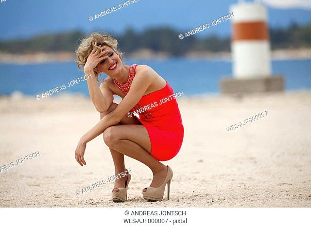 Greece, Young woman crouching on sand at sea, smiling