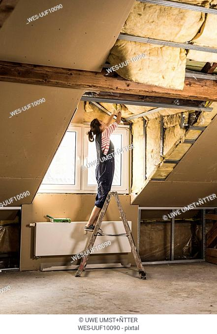 Young woman mounting insulation in her new home