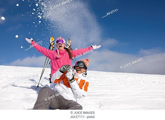 Skiers throwing snow on ski slope