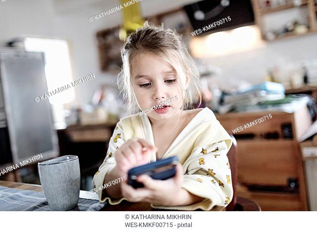 Portrait of little girl sitting at breakfast table in the kitchen using smartphone