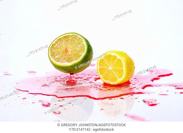 A lemon and lime are dropped onto red liquid making a splash