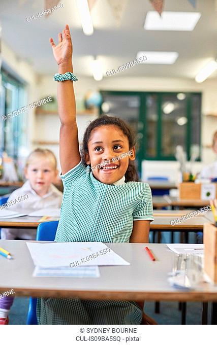 Schoolgirl with hand up in classroom at primary school