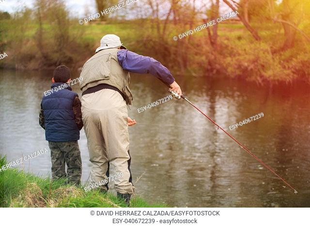 Father and son fishing on the river at sunset in autumn season