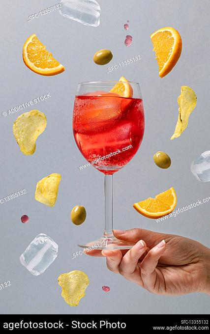 Crop female with glass of red alcohol cocktail garnished with orange slices and green olives above ground on gray background
