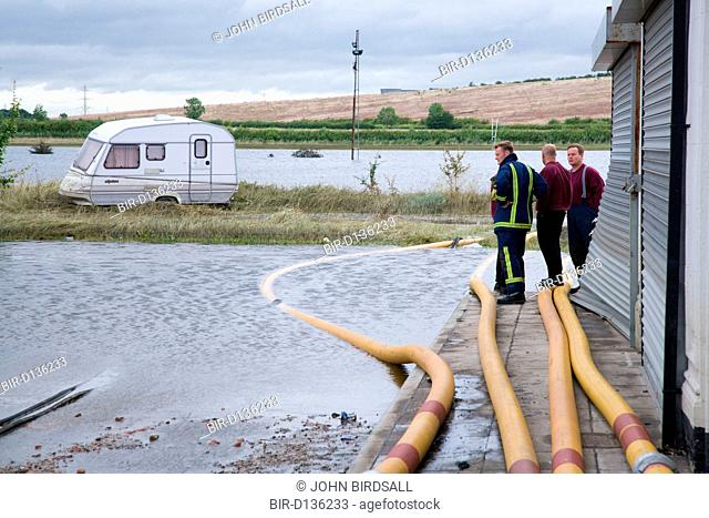 Members of the fire rescue service survey damage caused by flooding at Toll Bar, South Yorkshire, July 2007