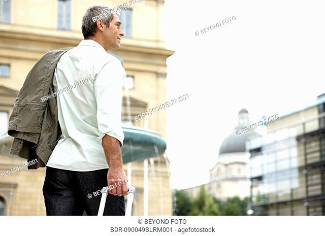 man walking through city street pulling carry-on