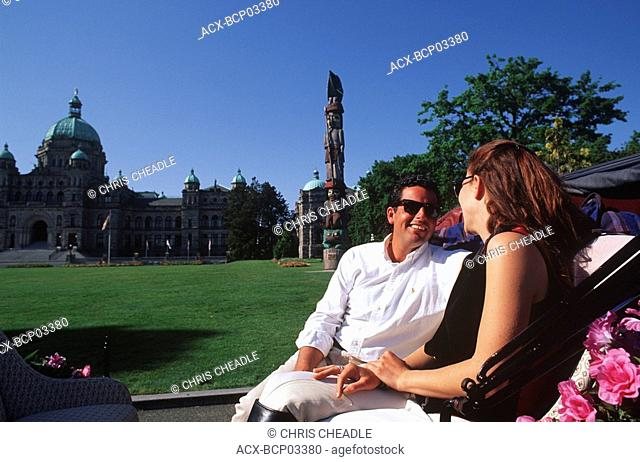 young couple enjoy horse carriage ride, legislature beyond, Victoria, Vancouver Island, British Columbia, Canada