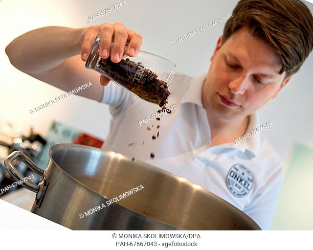 Phillip Roberts, CEO of Onkel GmbH, pours dried coffee cherry shells (also kwown as cascara) into a pot of water for brewing beer in his apartment...