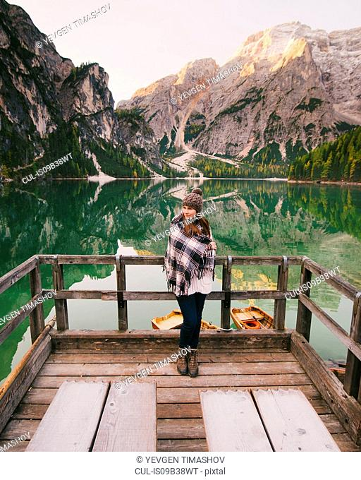 Woman leaning against wooden railings, Lago di Braies, Dolomite Alps, Val di Braies, South Tyrol, Italy