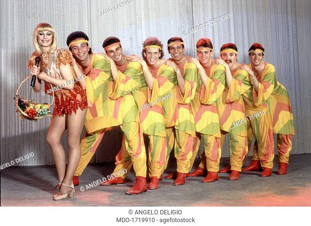 Dancers in a queue behind Raffaella Carrà. Italian showgirl and TV presenter Raffaella Carrà (Raffaella Pelloni) holding a fruit basket wearing a stage costume...