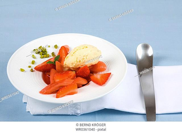 Strawberries on a plate with vanilla ice cream