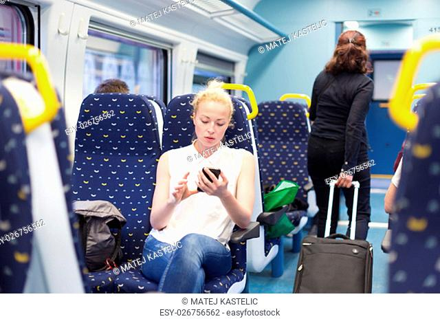 Woman workin on smart phone while traveling by train. Business travel concept