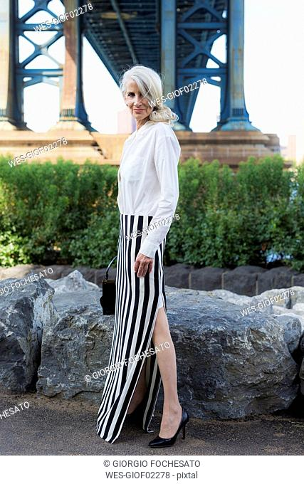 USA, Brooklyn, Dumbo, stylish mature woman standing in front of Manhattan Bridge