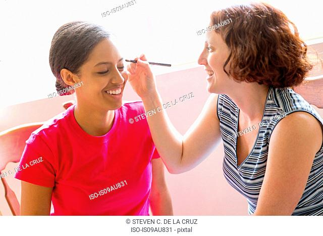 High angle view of young woman using makeup brush to apply make up to friends face