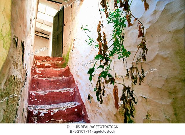 Staircase with open door to the end in an abandoned house, Menorca, Balearic Islands, Spain