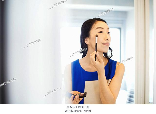 A business woman preparing for work, doing her make up