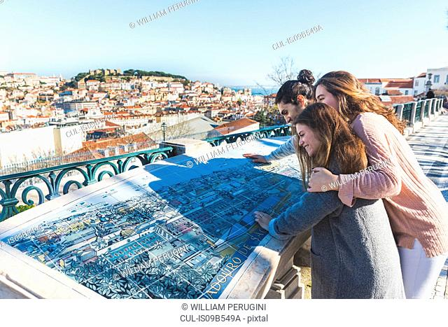 Three friends, looking at tourist map, Lisbon, Portugal