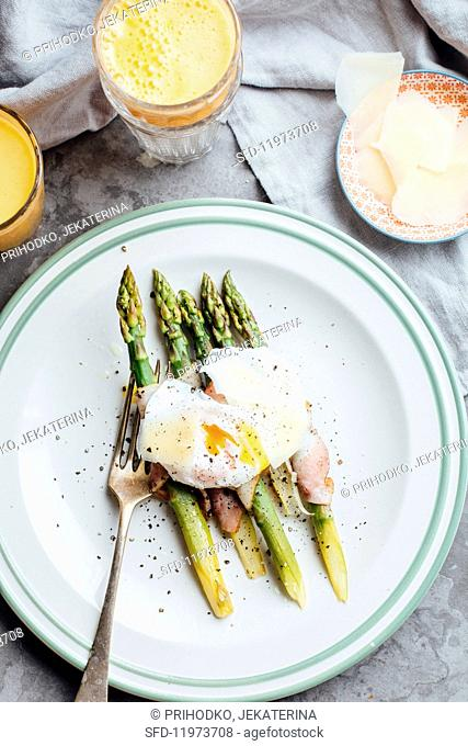 Roasted asparagus wrapped in bacon with a poached egg