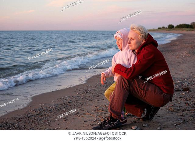 Daughter with Mother at Sunset on Beach by Sea