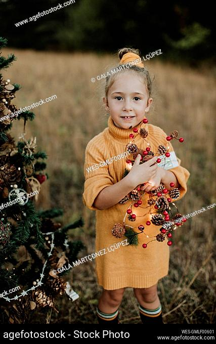 Girl holding decorations while standing by Christmas tree at countryside