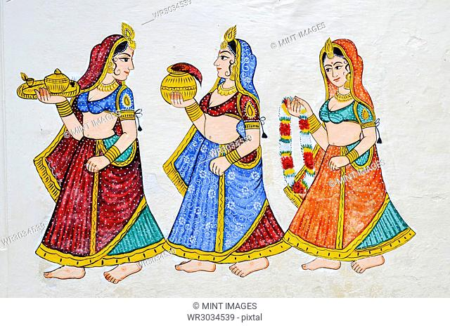 Mural of three women wearing saris and carrying gifts in Udaipur City Palace