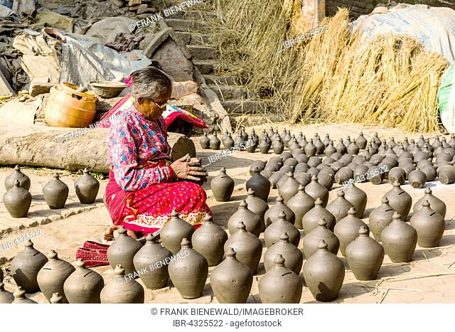 A woman is working at pottery in the streets, Bhaktapur, Kathmandu, Nepal