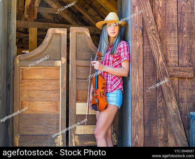 Teen girl violin player American West saloon