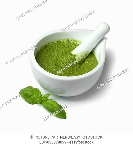 Green homemade Italian pesto in a mortar on white background