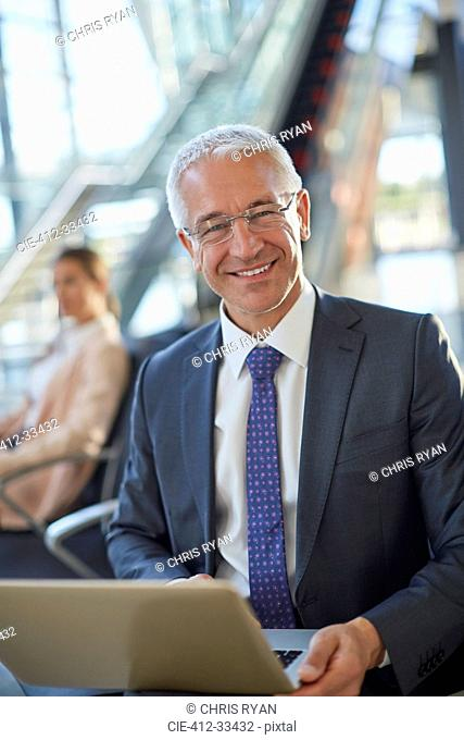 Portrait smiling businessman using laptop in airport