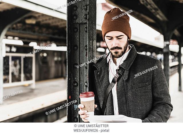 Young man waiting at metro station platform, reading documents