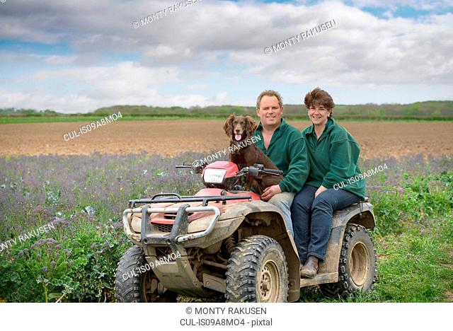 Farmer, wife and pet dog on quad bike in field of organic farm