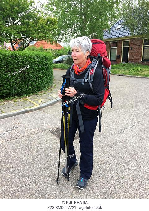 A mature woman, equipped with walking poles and backpack, is all set to walk the Pieterpad, a 500 kilometer walking trail from the north of Holland to...