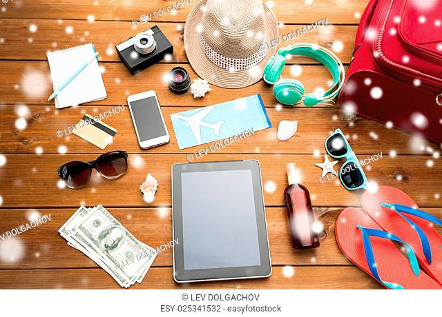 vacation, winter holidays, tourism and technology concept - tablet pc computer, airplane ticket and travel stuff over snow