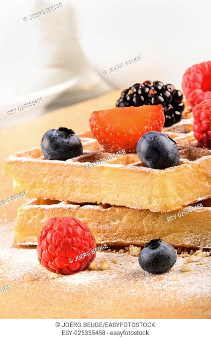 freshly baked waffles with sweet fruits, blueberry, strawberry, blackberry, raspberry and powdered sugar