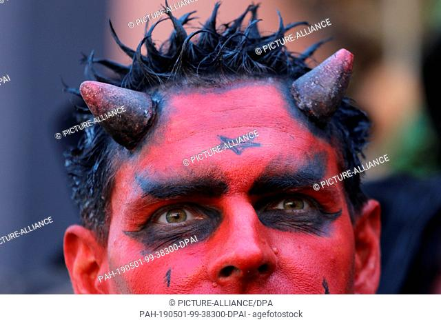 dpatop - 30 April 2019, Saxony-Anhalt, Wernigerode: A man disguised as a devil walks through the city to Walpurgisfest. Tens of thousands celebrated the...