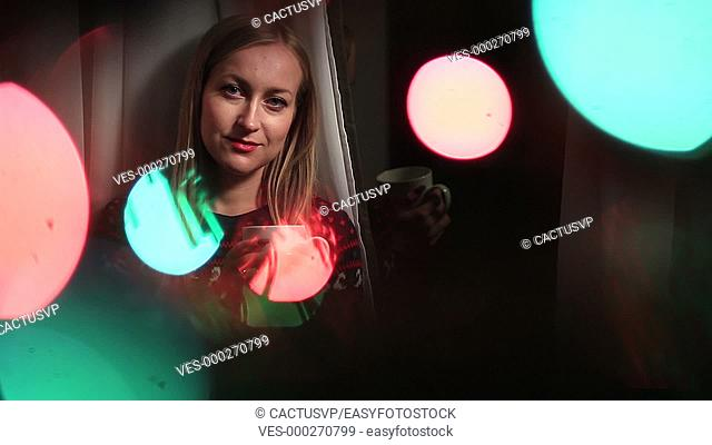 Attractive woman in bokeh circles of Xmas lights