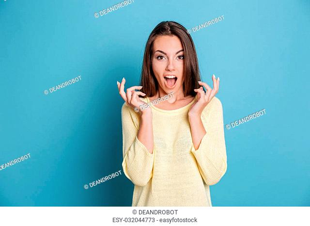 Surprised young beautiful girl looking at the camera isolated on the blue background