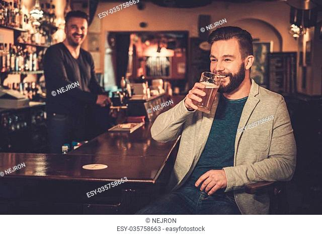 Stylish man paying for beer by cash euro to bartender in pub