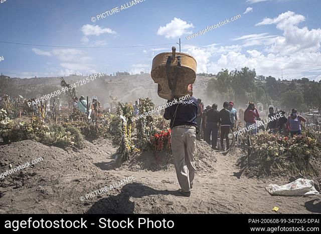 07 June 2020, Mexico, Chalco: A man carries a musical instrument in a cemetery while relatives say goodbye to their relatives who died because of or with...