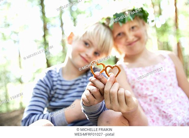 Boy and girl in forest holding heart-shaped pretzel pastry